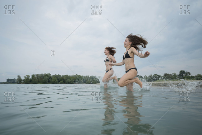 Two girls while bathing in the lake, quarry pond Liedolsheim, Dettenheim, Baden-Wurttemberg, Germany
