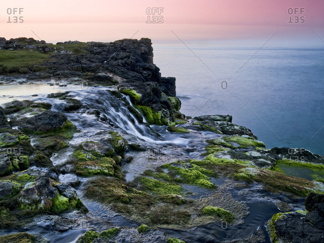 Northern Ireland, Antrim, Causeway Coast, waterfall on the coast, evening mood
