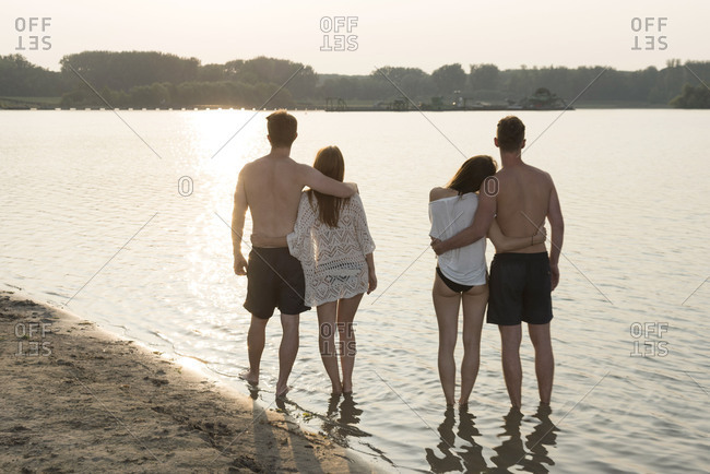 Two young couples in the sundown on the quarry pond Liedolsheim, Dettenheim, Baden-Wurttemberg, Germany