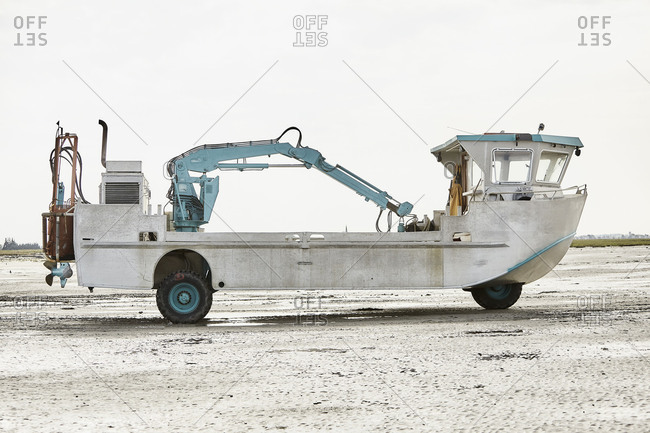 Amphibious vehicle with construction machine on a beach on the Atlantic, cloudy sky