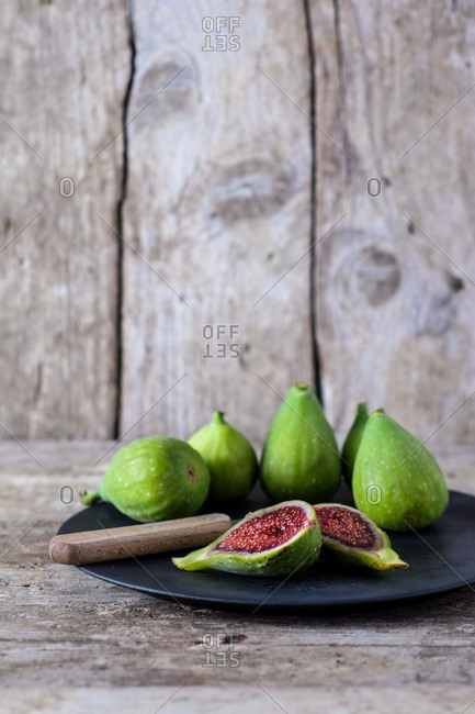 Just harvested green figs on a plate,  on an old wooden table, in front of an old wooden wall