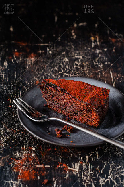 A piece of dark Paleo Low Carb chocolate cake on black background
