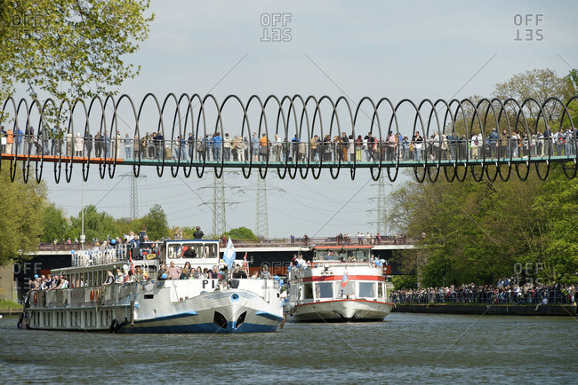 May 29, 2018: Ship parade on the Rhine�Herne Canal with view to the footbridge Slinky Springs to Fame, architect Tobias Rehberger and the gasometre, Oberhausen, North Rhine-Westphalia, Germany