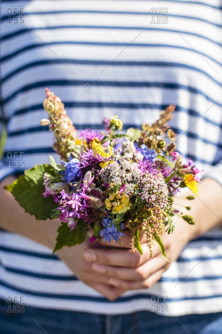 April 23, 2018: A young woman is holding a bouquet of freshly picked wildflowers, Europe, Denmark, Bornholm,