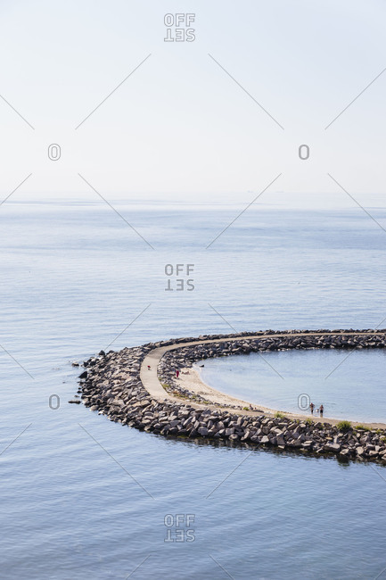 April 23, 2018: Bathers at the pier of Vang, former port of debarkation of the granite quarry, Europe, Denmark, Bornholm,