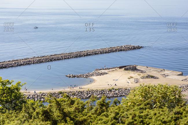 April 23, 2018: Bathers at the pier of Vang, former port of debarkation of the granite quarry, Europe, Denmark, Bornholm,