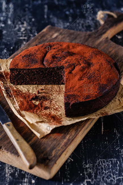 Dark chocolate cake on an old wooden board, parts of it already cut off