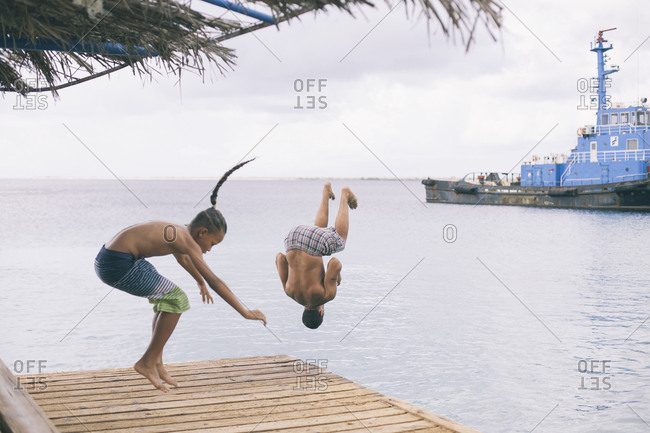 March 23, 2018: Two guys jumping on a dock to the water