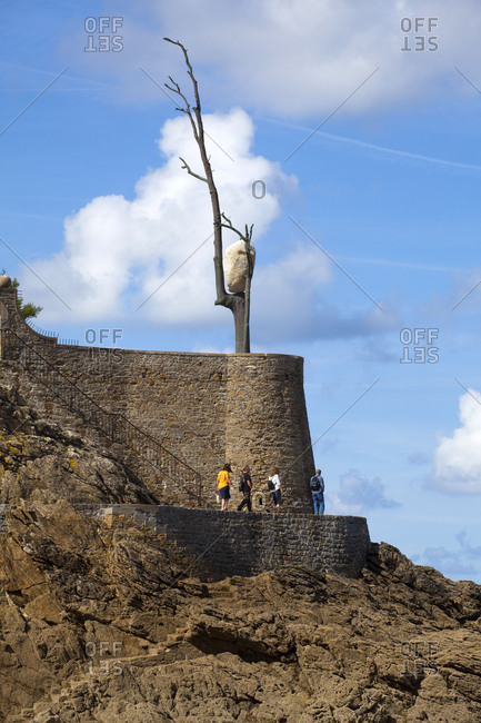 April 23, 2018: Breton seaside resort Dinard, tree, stone, curious balancing act
