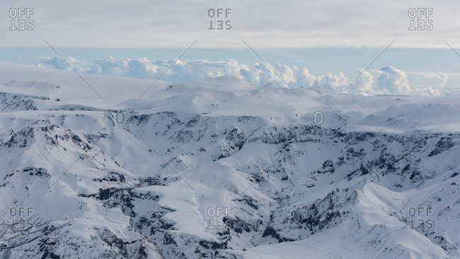 Icelandic snow-covered landscape, birds eye view, volcanic mountains and the Atlantic Ocean in the background