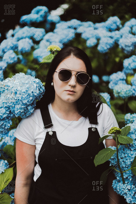 Portrait of a young woman wearing overalls and sunglasses standing among blooming hydrangeas