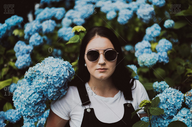 Portrait of a young woman wearing sunglasses standing among blooming hydrangeas