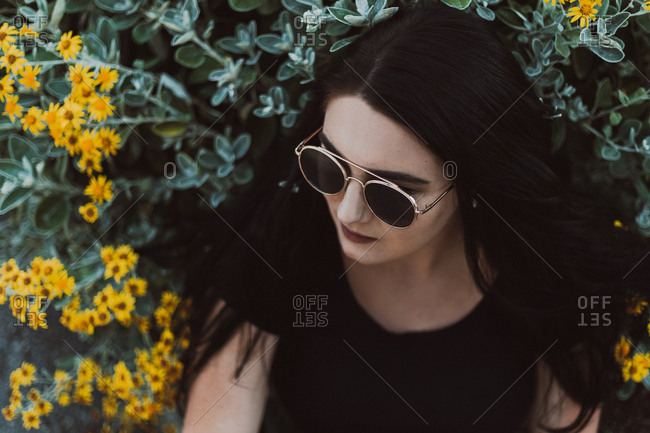 Portrait of a young woman with dark hair wearing sunglasses standing next to wildflowers