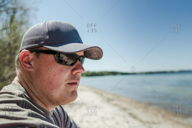 Man in ball cap and dark sunglasses enjoying view of beach