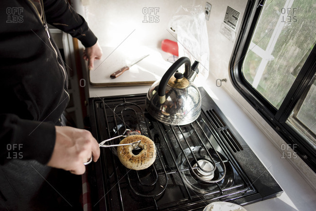 Cropped view of man turning whole bagel on RV stovetop