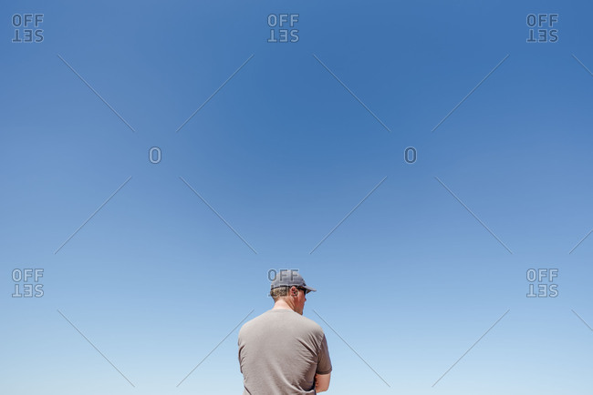 Back view of man standing with arms crossed in from of large clear sky