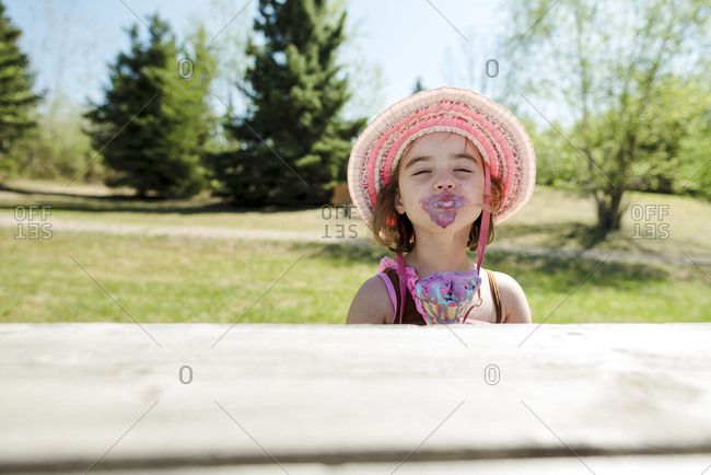 Messy girl making silly face with melting ice cream cone alone at outdoor picnic