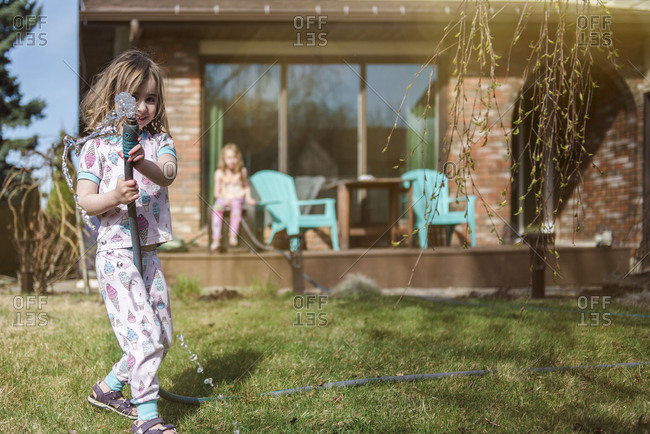 Little girl playing with water hose in sunny backyard