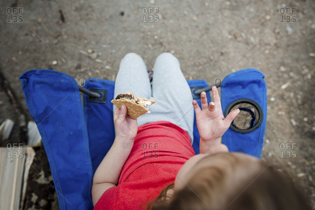 Overhead view of small child eating smore in camping chair outside