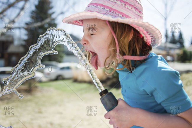 Young girl licking water spraying out of rubber hose