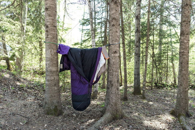 Unattended sleeping bag hanging from campsite trees