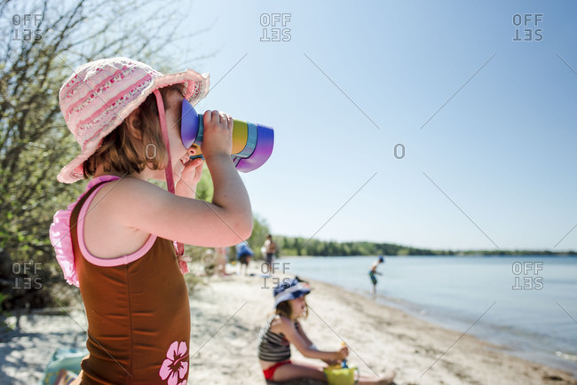 Little girl looking at ocean through toy binoculars on the beach