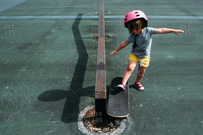 Toddler in pink helmet riding a skateboard