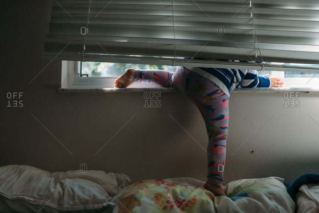 Toddler girl playing with window blinds