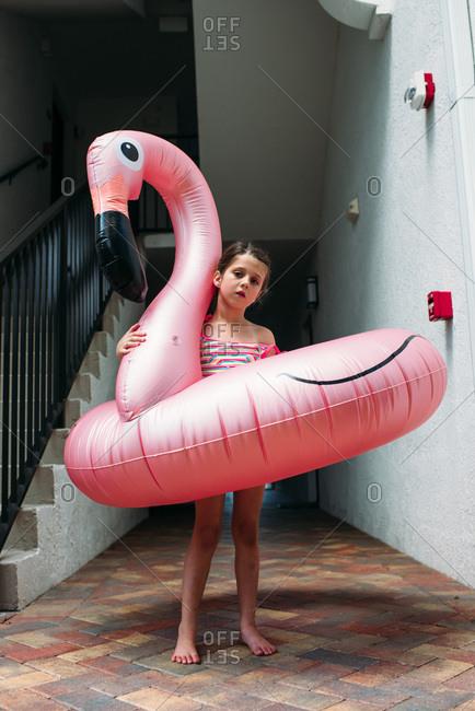 Little girl with flamingo pool float