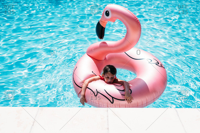 Little girl swimming with flamingo float in a pool