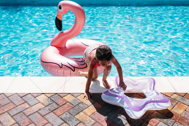 Little girl with flamingo float in a pool
