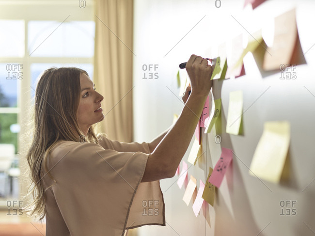 Woman writing on sticky note at the wall