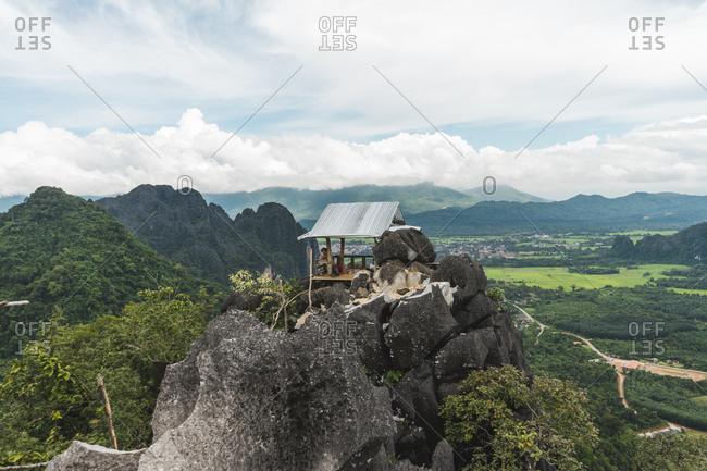 Laos- Vang Vieng- man in hut on top of rocks overlooking landscape of rice fields