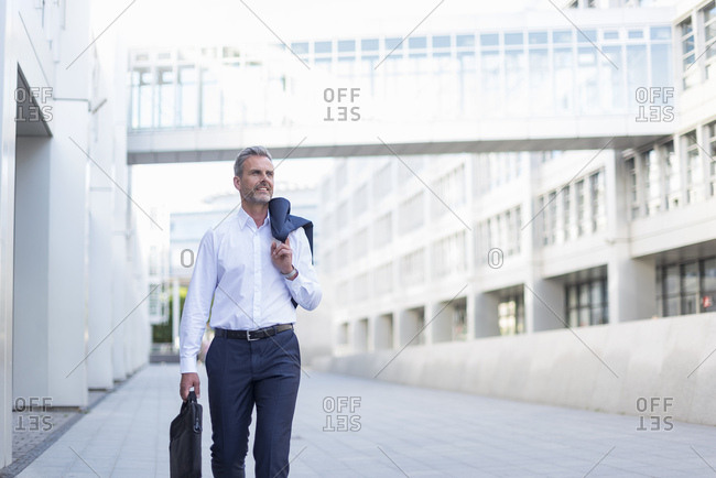Businessman with laptop bag walking at courtyard of modern office buildings