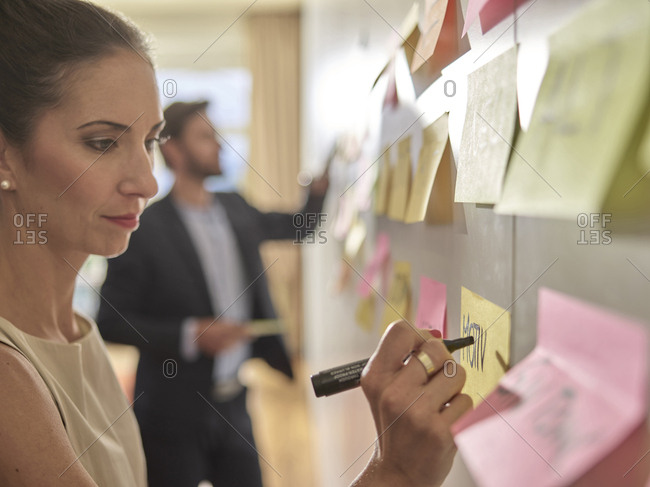 Colleagues writing on sticky notes at the wall