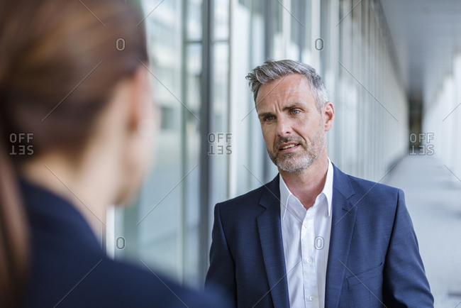 Portrait of skeptical businessman face to face to his business partner