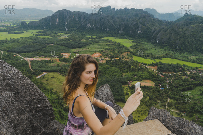 Laos- Vang Vieng- young woman on top of rocks taking a selfie