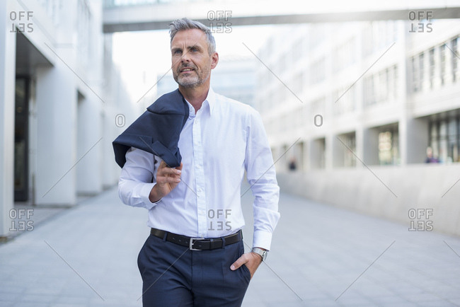 Portrait of businessman walking at courtyard of modern office building