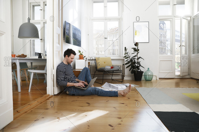 Man sitting in floor- using laptop- working from home
