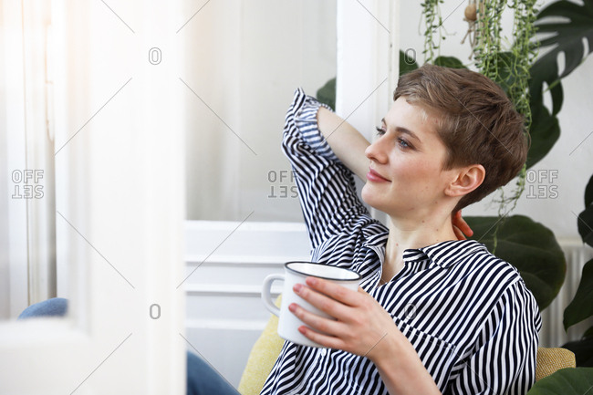 Happy woman sitting relaxed at window- drinking coffee