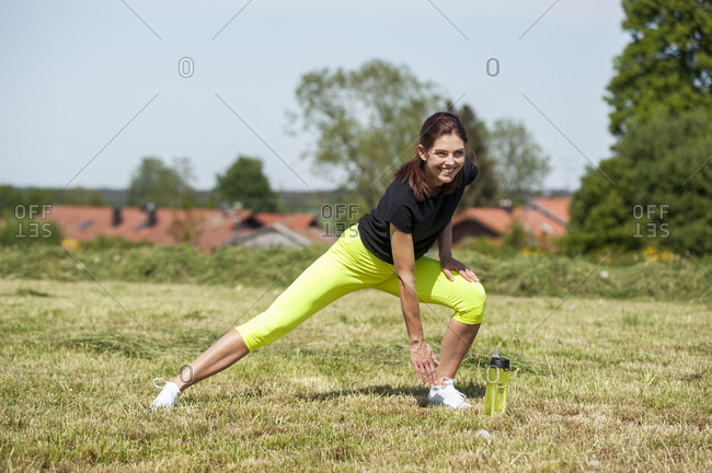 Woman doing stretching exercise on meadow