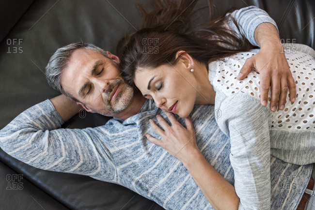 Relaxed couple lying on couch at home