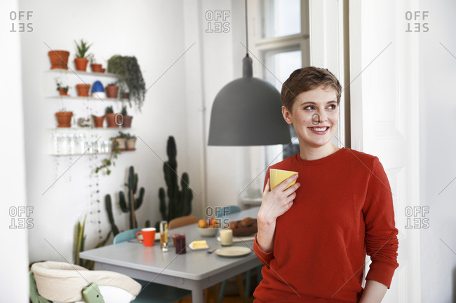 Woman standing in her comfortable home- drinking coffee