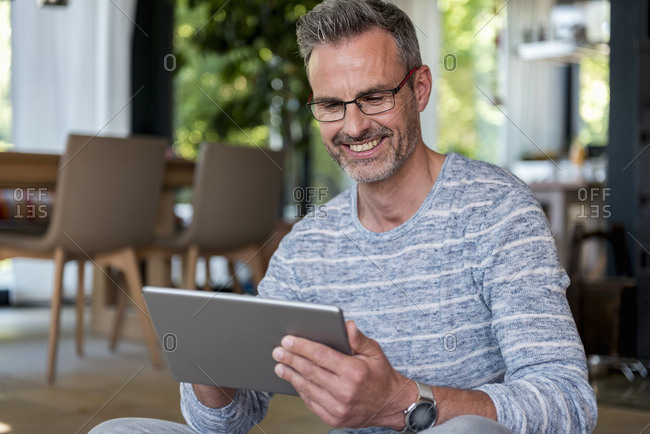 Smiling mature man at home using a tablet