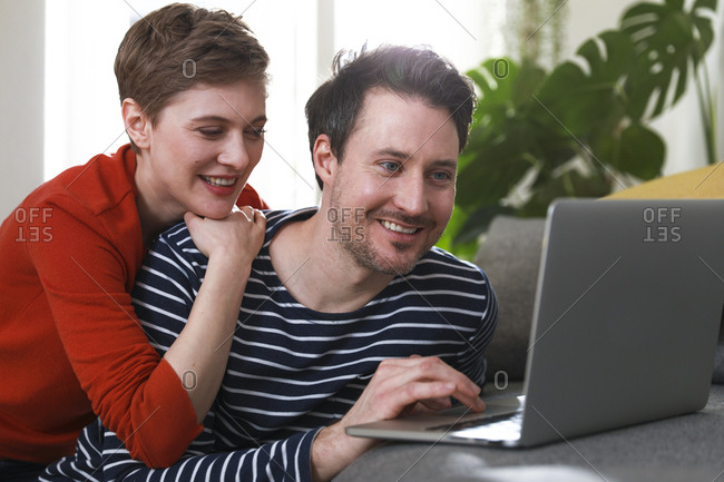 Couple sitting at home- using laptop
