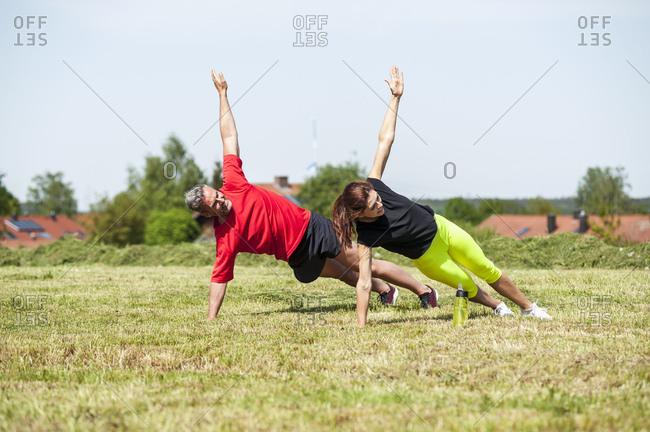 Couple doing side plank exercise on meadow