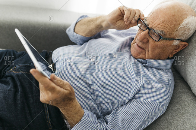 Senior man surfing the internet on a tablet while lying on the sofa