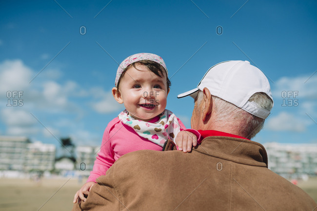 France- La Baule- portrait of baby girl on grandfather's arms on the beach
