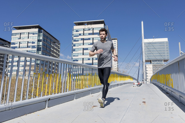 Sportive man running on a bridge in the city