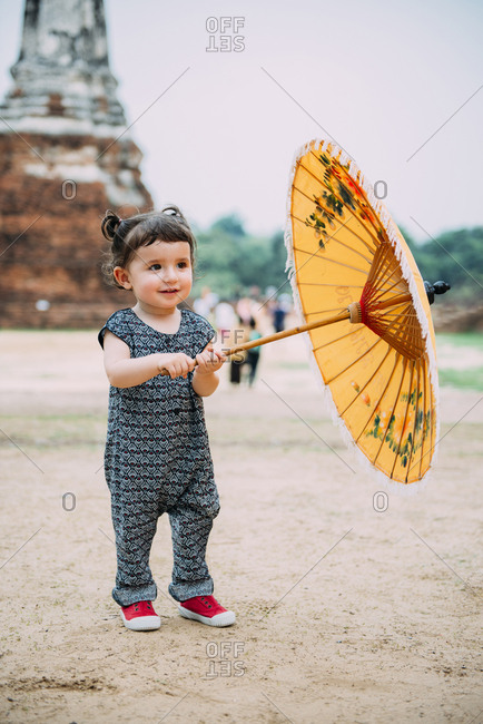 Thailand- Ayutthaya- Wat Chaiwatthanaram- portrait of toddler with yellow umbrella